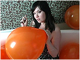 Video clip for sale of Xev sitting in a balloon-filled bathtub, inflating and popping balloons