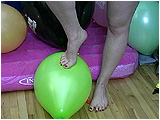 Video clip of Kat foot popping balloons with her bare feet