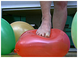 Kedra uses her feet to tease and pop balloons