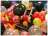 daphne posing with a room full of balloons