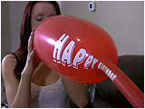 Video clip for sale of Holly blowing to pop two giant birthday hot dog balloons
