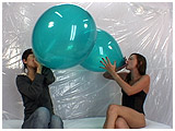 Alice and Pixie blow to pop a pair of green jewel toned balloons