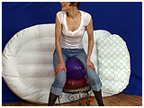 Alice pops balloons using her jeans covered bum