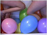 Video clip for sale of Holly and Raven barefoot-popping as many balloons as they can in the bathtub