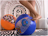 Video clip for sale of Holly popping beachballs with her bare feet