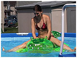 Debby gets really wet while playing with an inflatable alligator
