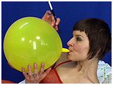 Alice smokes using a cigarette holder with her balloon